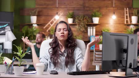 en tête : Woman trying to meditate while her colleagues in the background are very stressed. They are throwing papers in the air. Slow motion shot. Conceptual footage
