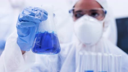 banka : Female scientist in a laboratory picking up and holding a smoking blue fluid in a bottle. Fluid reaction. Dostupné videozáznamy