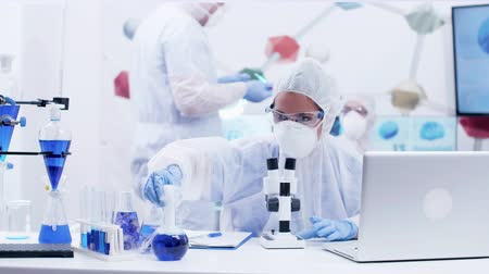 banka : Woman scientist looking through microscope in laboratory wearing protection equipment. Scientist taking a flask with reactive blue solution. Dostupné videozáznamy