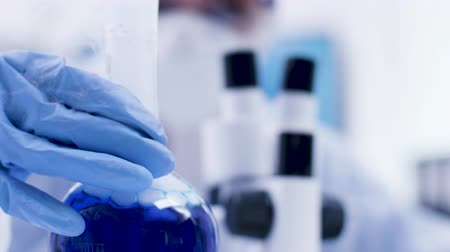 koníčky : Close up of blue fluid in a bottle smoking in science laboratory. Female scientis in coverall equipemnt in the background. Dostupné videozáznamy