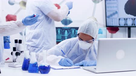 artigos de vidro : Research scientist in chemical industry working with smoking blue fluid wearing coverall equipment. Scientist colleague helping with research. Vídeos