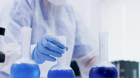 фельдшер : Female scientist holding and looking at a blue solution with reagent in research laboratory