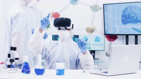 amostra : Female scientist with virtual reality headset in modern chemistry laboratory