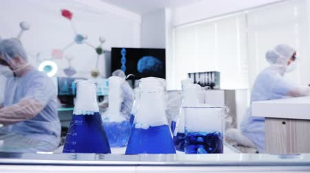farmacologia : Smoking blue liquid on cart in a modern science laboratory. Scientist in coverall protection equipment.