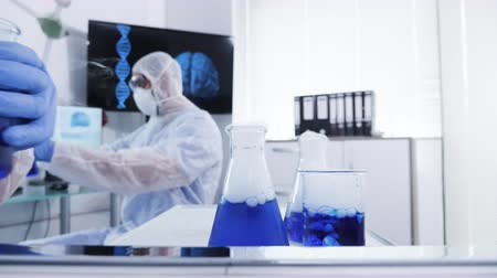 farmacologia : Pov of scientist in coverall equipment taking blue liquid from a moving cart in laboratory. Modern chemistry.