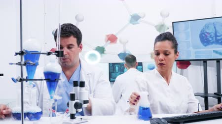 proveta : Female scientist in white coat and her assistant working with in modern lab research. Assistant helping female scientist with research. Smoking blue liquid. Vídeos