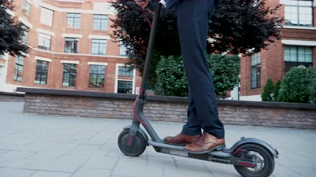 ambientalmente : Unrecognisable man in business suit coming to work on electric scooter