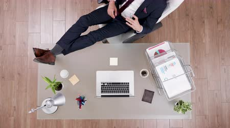 rentável : Top view of businessman in suit staying relaxed with feet on his office desk. Modern looking office.