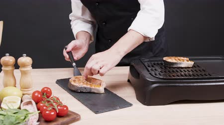 filet : Cook preparing a dish from frying salmon fillet seasoned with mediterranean herbs. Stock Footage