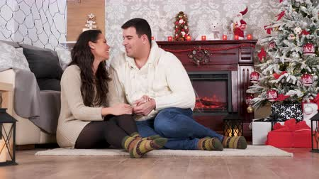 Beautiful couple in Christmas decorated room chatting on the floor. They are relaxing and waiting for guests