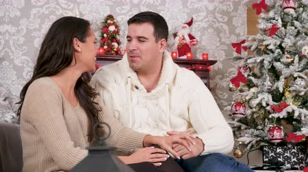 Gorgeous caucasian couple spending time together in Christmas eve. They are in a beautiful decorated room and there is fireplace behind them Wideo