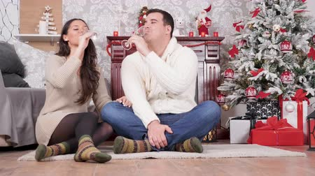 Caucasian couple having an intimate moment at Christmas eve. They drink champagne and are happy Wideo