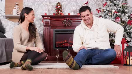 Man gives woman a big red box with a present. They are in a Christmas decorated room. Happy family