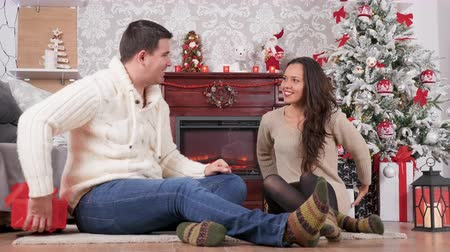 Couple giving each other presents in Christmas eve in beautiful room with a fireplace. Celebration, love and romance Stockvideo