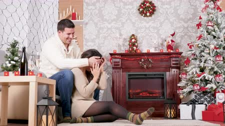 Happy inlove couple laughing and spending time together in Christmas decorated room. Love and Xmas celebration Stockvideo