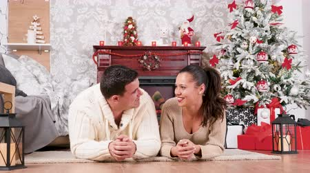 Couple on the floor laughing and having a good time in Christmas eve. There is a fireplace in the background