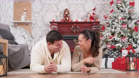 Inlove couple laying on the floor, sharing a tender and happy moment in a beautiful Christmas decorated room. Xmas tree and a firplace in the background