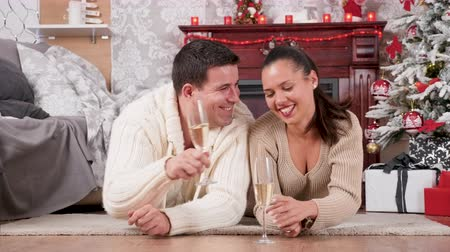 Happy couple spending time together in Christmas eve. They drink champagne