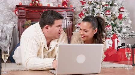 Happy smiling couple shopping online for Christmas gifts. Beautiful decorated room