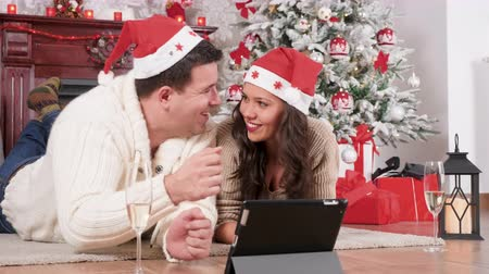 Happy couple in Christmas decorated room ordering presents online using a digital tablet