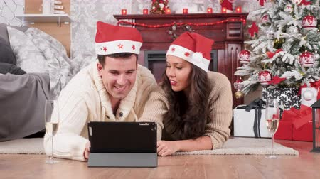 Couple lying on the floor in Christmas eve shopping online using a tablet PC. Beautiful ornated tree in the background Stockvideo
