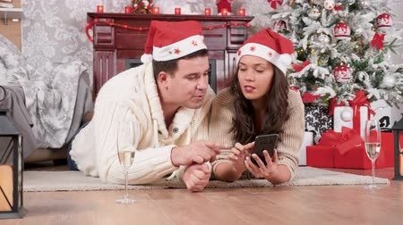 Smiling couple sitting on the floor shopping online using a smartphone in Christmas decorated room
