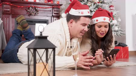 Happy inlove couple lying on the floor in Christmas decorated room using a smartphone Wideo