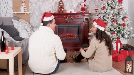 Inlove couple sitting on the floor in front of a fireplace in Christmas decorated room, dolly shot