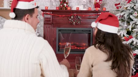 Caucasian couple spending their Christmas in front of a fireplace. Selective focus