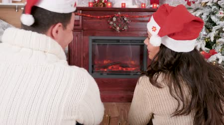 Relaxed couple enjoying a glass of champagne in front of fireplace in Christmas eve, static shot rack focus