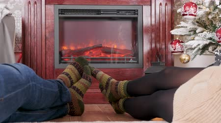 Man and woman feet in front of the fireplace next to a Christmas decorated tree, dolly shot