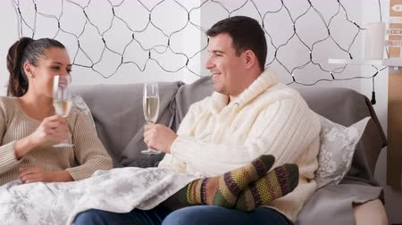 Couple drinking champagne sitting on the sofa in Christmas decorated room, selective focus