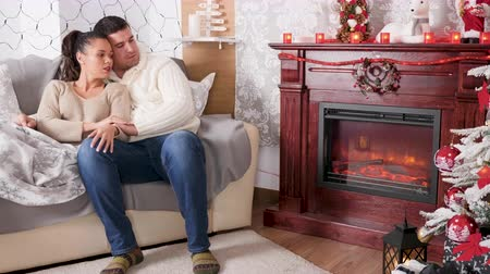 Beautiful couple lying together in the bed looking at the fireplace in Christmas decorated room.