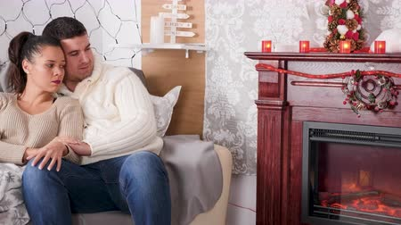Happy inlove couple looking at the fireplace sitting on the sofa in Christmas decorated room