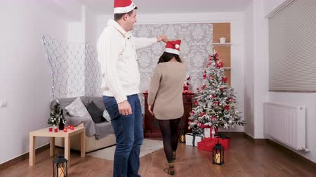 Happy couple celebrating Christmas dancing in the living room