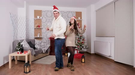 Caucasian couple dancing with champagne glasses in hands, Christmas decorated room Stockvideo
