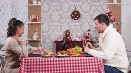 Caucasian couple at Christmas dinner clinking their glasses with champagne