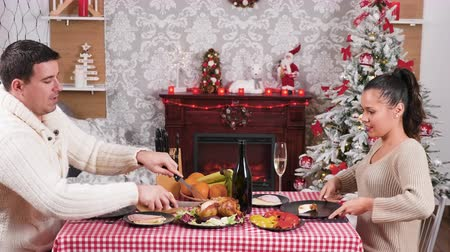 Caucasian couple enjoying a Christmas dinner and clinking glasses with champagne