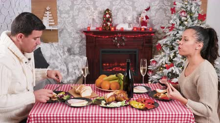 Couple eating and clinking glasses with champagne at Christmas dinner table