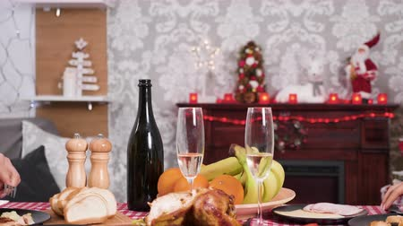 Couple at Christmas dinner eating together and clinking glasses of champagne Wideo