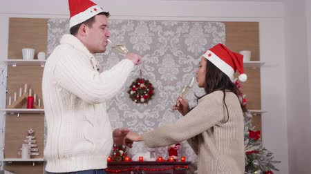 Caucasian couple dancing and drinking champagne in Christmas decorated room