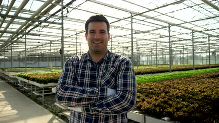 Young farmer in a modern greenhouse with high end technology. Business in agriculture
