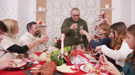 jeść : Man making a toast at family dinner with champagne. Celebrating christmas.