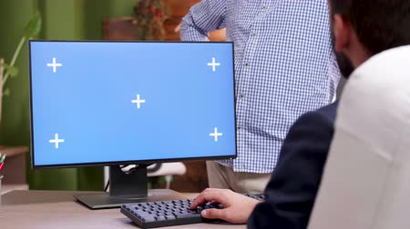 dizgi : Businessman typing on computer with green screen in his office and shaking hands with colleague.