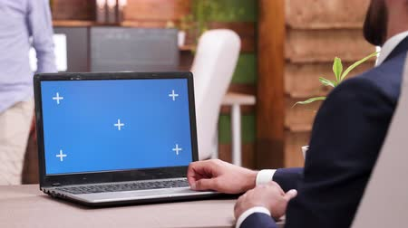 back side : Young bearded businessman typing on laptop with green screen Stock Footage