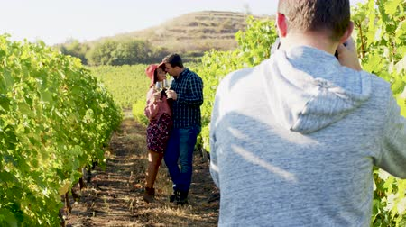 photoshoot : Caucasian couple being photographed in a vineyard. Handheld footage. Shot in 6K on cinema camera Stock Footage