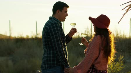 winemaking : Couple holding hands and tasting white wine at the sunset. Shot in 6K on cinema camera