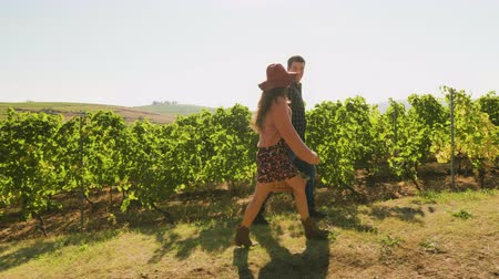 grape basket : Couple carrying a big basket with white grapes in a beautiful vineyard, slow motion footage