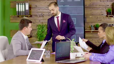 brifing : Bearded businessman in suit giving his team to analyze charts in the conference room. Stok Video