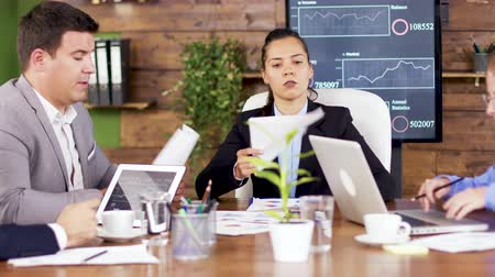 briefing : Female team leader giving his team financial charts. Female director having a discussion with her team. Stock Footage